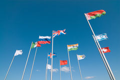Flags waving across blue sky Stock Photo