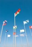Flags waving across blue sky Stock Image