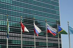 Flags outside united nations building in new york. Flags waving outside united nations building in manhattan new york stock photography