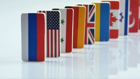 Flags on white surface. The domino effect with tile of flags of different countries of the world. The camera is stationary. Starting with the Russia stock video