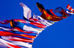 Flags in the Wind. Colorful flags flapping in the wind on blue sky Royalty Free Stock Photo