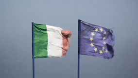 Flags wind Italy EU worn. Two national flags, Itay and the European Union, waving in the wind on a windy day. Worn-out, tarnished, bleached textile stock video