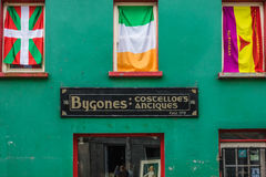 Flags in windows. Irish and two other flags in windows above an old antiques shop in Limerick, Ireland Stock Images