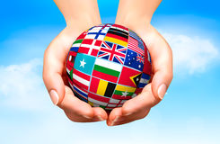Flags of the world in globe and hand. Royalty Free Stock Image