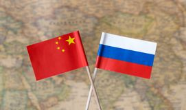 Flags of Russia and China over the world map, political leader countries concept image. Flags of the world political leader countries over the world map stock images