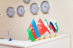 Flags of the world on the table, clock of the room. On the wall royalty free stock images