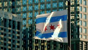 Cinematic Chicago flag waving at sunset. Flagstaff on the Golden Mile in Chicago city center. Chicago flag waving in the windy city of Chicago stock footage