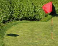 Flagstick Flutters in Breeze. Shadow to left - motion blur on flag/pole Stock Photography