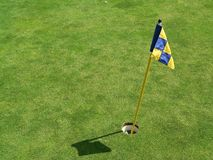 The flagstick and hole. A mini flag stick on the putting green Royalty Free Stock Photography