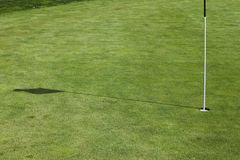 Flagstick hole on a putting green in a golf course. Stock Image