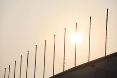 Flagsticks stand in great numbers,. In the sunset ,Some flagsticks stand in great numbers Royalty Free Stock Images