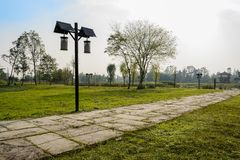 Flagstone path in grassy lawn near pond in sunny winter afternoon. Flagstone path in grassy lawn near the pond in sunny winter afternoon,Chengdu,China stock photos