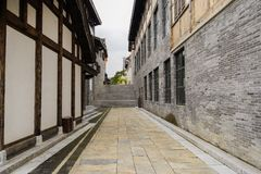 Flagstone alley between old-fashioned buildings in cloudy afternoon. Flagstone-paved alleyway between old-fashioned buildings in cloudy afternoon,Qingyan town stock photo