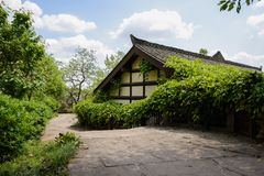 Flagstone-paved path before hedged building in Chinese tradition. Flagstone-paved path before hedged building in traditional style on sunny day,Wufeng town Royalty Free Stock Photos