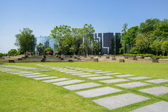 Flagstone pavements in grassy lawn before modern building on sun Stock Image