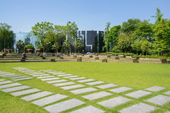 Flagstone pavements in lawn before modern buildings on sunny sum Stock Photography