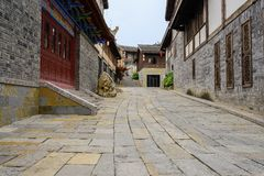 Flagstone street on upslope between old-fashioned tile-roofed bu. Flagstone paved street on the up-slope between old-fashioned tile-roofed buildings in cloudy royalty free stock photography
