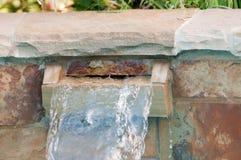 Flagstone waterfall on side of swinning pool Royalty Free Stock Images