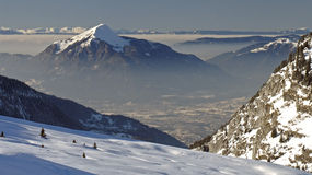 Flaine - snowy peak. View of a snowy peak surrounded by misty cloud in the valley below. Flaine, France stock photos