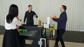 Flair bartending performed by two bartenders and woman watching by the bar stock footage