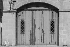 Flaked gate on Malta. Flaked gate in historic part of Valletta. Entrance to an abandoned house on the island of Malta. Black and white picture Royalty Free Stock Images