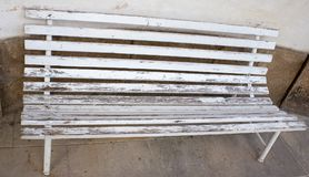 Flaked white garden bench is standing by the wall. Flaked white garden bench is standing by the wall on a stone pavement Royalty Free Stock Photos
