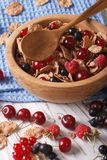 Flakes with fresh berries close up in a wooden bowl. vertical. Flakes with fresh berries close up in a wooden bowl on the table. vertical Royalty Free Stock Photography