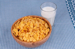Flakes and a glass of milk. Flakes in a wooden bowl and a glass of milk Stock Photography