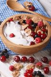Flakes with milk and berries close up in a wooden bowl. Vertical. Healthy breakfast: flakes with milk and berries close up in a wooden bowl. Vertical Royalty Free Stock Photo