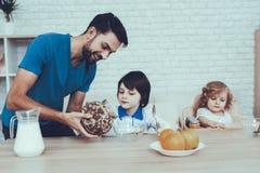 flakes mjölkar Fader av två pojkar frukost royaltyfria bilder