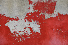 Flakes of old red paint on grey concrete wall. Flakes of old vintage grungy bright vivid red paint on grey concrete wall royalty free stock photos