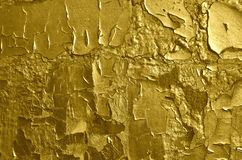 Texture of the cracked peeling golden graffiti paint