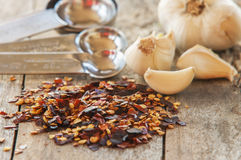Flakes of red hot chili peppers with garlic. Close up Stock Photo