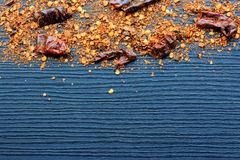 Flakes of red hot chili peppers on wood background Stock Photos
