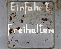 Flaking old weathered German inscription. `Keep entrance free`, on an ugly grey wall with too little paint and spots of rust, concept royalty free stock photo