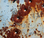 Flaking paint and bullet holes on rusty metal plate Stock Photography