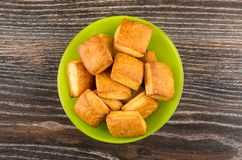 Flaky biscuits in green bowl on dark wooden table Stock Images