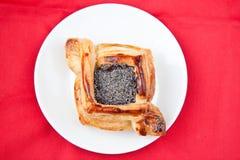 Flaky croissant with poppy. Freshly baked flaky croissant with poppy on a red background Royalty Free Stock Image