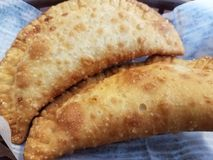 Flaky fried empanadas. Two delicious flaky fried golden brown empanadas Royalty Free Stock Image