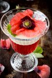 Flaky fruit jelly in glasses decorated with. Fruit desserts with flowers served in glasses stock images