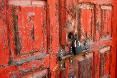 Flaky paint and a new padlock. Old fire-station door painted red peeling paint. Door closed with a modern padlock Stock Image