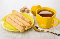 Flaky sticks in saucer, tea, teaspoon, lemon, sugar on table Royalty Free Stock Photo