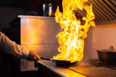 Flambe羊羔烹调与在煎锅的火的牛里脊肉 一商业厨房烹调的专业厨师 人油煎 库存图片