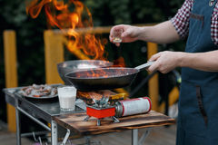 flambe Τηγανισμένα θαλασσινά στο τηγάνι σιδήρου ο κύριος μάγειρας χύνει το οινόπνευμα και την πυρκαγιά Στοκ εικόνες με δικαίωμα ελεύθερης χρήσης