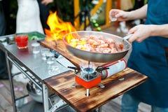 flambe Τηγανισμένες γαρίδες βασιλιάδων στο τηγάνι σιδήρου ο κύριος μάγειρας χύνει το οινόπνευμα και την πυρκαγιά Στοκ Φωτογραφία
