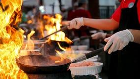 在一个商业厨房里烹调Flambe样式的专业厨师 库存图片