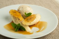 Flambe Banana with butter rum ice cream with caramel sauce. On a cream color plate and tan woven placemat Stock Photo
