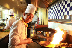 Flambe cooking. Portrait of chef flambe cooking in the kitchen Royalty Free Stock Photos