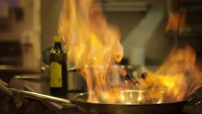 Flambe food in pan stock video footage