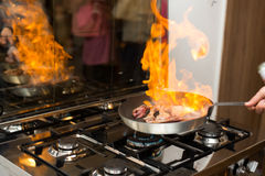 Flambe pan. Chef flambe lamb ribs in a pan Royalty Free Stock Photos